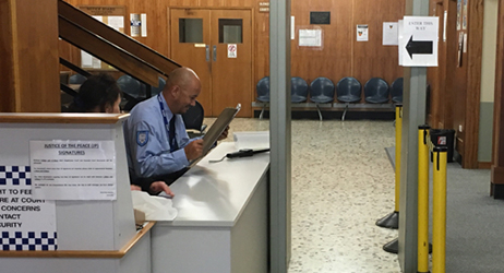 entrance to the Magistrates Court in Burnie: a man in the security guard uniform is standing next to the security gate