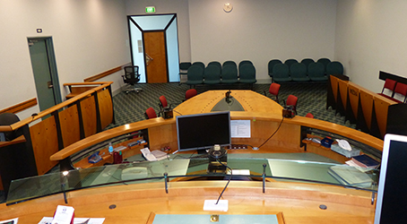 View from a Magistrate's chair at a court room with the oval table for prosecutors and laweyres, seats for media on the right and place for accused person on the left